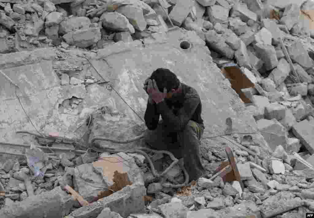 در پی گزارش حمله هوايی نيروهای حکومتی سوريه به مواضع شورشيان در حلب در شمال سوريه بسيآری از ساختمانها با خاک يکسان شدند. اين جوان سوریهای در غم از دست رفتن عزيزانش در اين حملات میگريد.