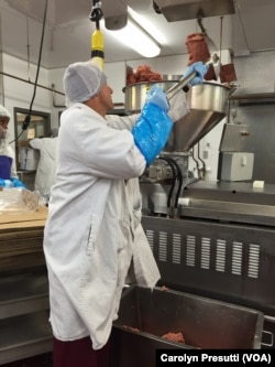 Nick Holubyckyj puts raw beef into the machine for compression and into bags.