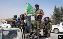 FILE - In this file photo released June 23, 2015, provided by the Kurdish fighters of the People's Protection Units (YPG), which has been authenticated based on its contents and other AP reporting, Kurdish fighters of the YPG sit on their pickup in the town of Ein Eissa, north of Raqqa city, Syria.