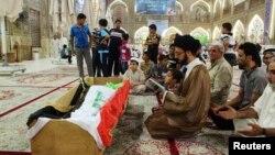 基地組織在巴格達兩所監獄星期一發動襲擊導致多人死亡﹐送殯者為被害人祈禱。
