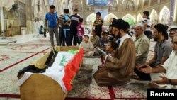 Warga Irak melakukan upacara pemakaman atas korban tewas dalam serangan militan terhadap penjara Taji, di pinggiran kota Baghdad (22/7).