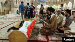 Mourners pray at the coffin of a victim killed during an attack on a prison in Taji, during a funeral at the Imam Ali shrine in Najaf, 160 km (100 miles) south of Baghdad, July 22, 2013.