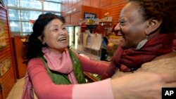 Young Soo Lee, dueña de una de las tiendas en donde se vendió uno de los billetes ganadores, en Atlanta, celebra la noticia. El establecimiento recibirá un premio de $1 millón de dólares.