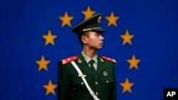 一名中国警察站在欧盟驻华代表团办公室外的欧盟旗帜前。