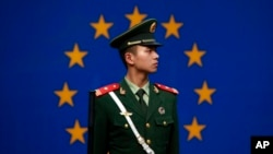 FILE - A Chinese policeman stands in front of the European Union flag outside the office of the European Union delegation to China in Beijing, Oct. 28, 2011. The chamber said the EU is unlikely to lift trade barriers this year because of fears Chinese exports are causing job losses.
