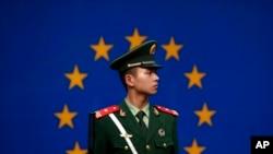 Seorang polisi China berjaga di depan bendera Uni Eropa di kantor delegasi Uni Eropa di Beijing, China (Foto: dok).