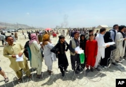 """Hundreds of people gather outside the international airport in Kabul, Afghanistan, Tuesday, Aug. 17, 2021. The Taliban declared an """"amnesty"""" across Afghanistan and urged women to join their government Tuesday."""
