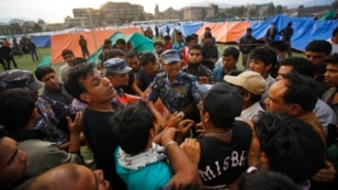 A Nepalese policeman argues with earthquake victims before distributing tents in Kathmandu, Nepal, April 26, 2015.