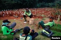 Para petugas penggali kuburan beristirahat di sebuah kompleks pemakaman jenazah pasien Covid-19, di Jakarta. (Foto: Reuters)