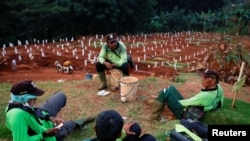 Para petugas penggali kuburan beristirahat di sebuah kompleks pemakaman yang disediakan pemerintah untuk jenazah pasien Covid-19, di Jakarta, 22 April 2020. (Foto: Reuters)