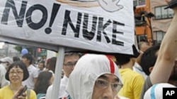 Anti-nuclear demonstrators wearing protective suits march down streets in Tokyo, Japan, June 11, 2011