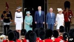 Britain's Queen Elizabeth II stands with President Donald Trump, center, and first lady Melania Trump, left, Britain's Prince Charles and Camilla, Duchess of Cornwall, right, during a ceremonial welcome in the garden of Buckingham Palace in London, June 3