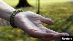 Cheryl Ecker menggunakan gelang yang terbuat dari tali sepatu tentara milik anaknya, Michael, di Champion, Ohio. Michael (25 tahun), veteran perang Iraq, bunuh diri di halaman belakang rumahnya dengan menembak kepalanya sendiri dengan pistol (Foto: dok). Laporan CDC mengungkapkan bahwa kasus bunuh diri usia menengah di AS meningkat 30 persen.