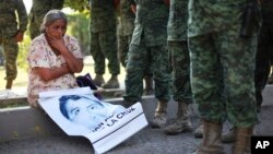 FILE - A woman who identified herself as the mother of missing student Adan Abarajan de la Cruz, 23, sits next to Mexican army soldiers standing in front of the entrance to the 27th Infantry Battalion base in Iguala, Mexico, Dec. 18, 2014.