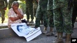 지난해 12월 멕시코 이구알라의 군부대 앞에서 실종된 학생의 어머니가 아들의 사진을 들고 실종 학생들의 송환과 사건 해결을 요구하고 있다. (자료사진)