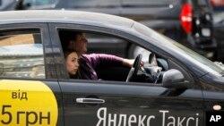 Kiev'de Yandex Taxi kullanan bir kadın.Litvanyalı yetkililer uygulamanın kullanıcıların kişisel bilgilerini izinleri olmadan topladığı ihtimaline karşı amu çalışanlarından uygulamayı telefonlarına yüklememelerini istedi