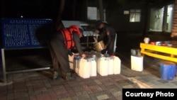 """太平岛上驻岛人员给渔民带来的水桶内装""""太平水""""(台湾海巡署提供)"""