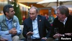 Presiden NBC Olympics Gary Zenkel (kiri), Presiden Rusia Vladimir Putin (tengah), dan ketua Komite Olimpiade AS Larry Probst dalam kunjungan ke USA House di Desa Olimpiade (14/2). (Reuters/Marianna Massey)