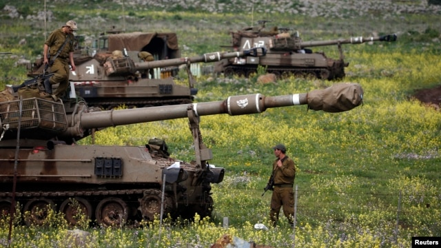 Israeli soldier stands by mobile artillery unit near town of Katzrin, Golan Heights, March 19, 2014.