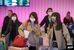 Para penumpang menggunakan masker untuk melindung dari virus corona saat tiba di Bandara Internasional Los Angeles, California, 22 Januari 2020.