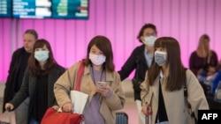Des voyageurs portent des masques pour se protéger contre la propagation du coronavirus à leur arrivée à l'aéroport international de Los Angeles, Californie, le 22 janvier 2020.