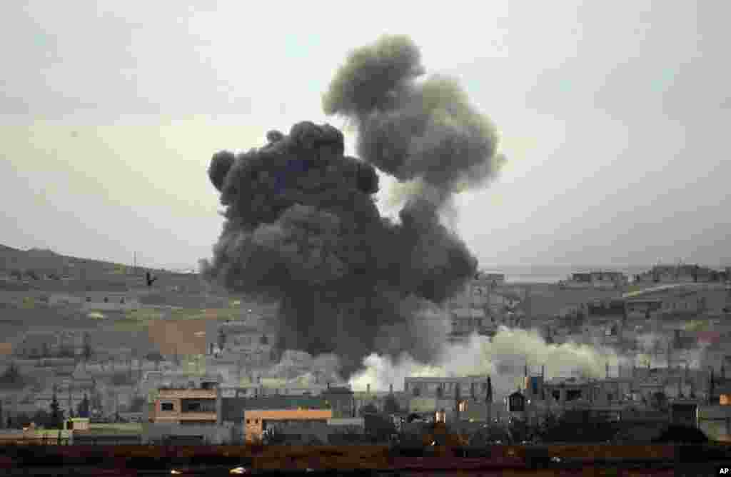 Thick smoke rises following an airstrike by the US-led coalition in Kobani, Syria, as seen from Mursitpinar on the outskirts of Suruc, Oct. 14, 2014.