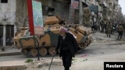 A Kurdish elderly man walks with a cane in Afrin, Syria, March 19, 2018.
