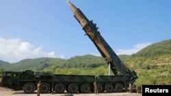 """Chiếc xe tải lớn sơn kiểu ngụy trang quân sự chở theo phi đạn đạn đạo liên lục địa giống hệt chiếc xe tải mà một ban chế tài của Liên Hiệp Quốc nói là """"có nhiều phần chắc"""" đã được chuyển đổi từ một chiếc xe tải chở gỗ của Trung Quốc."""