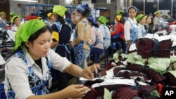 FILE PHOTO - Cambodian garment workers work inside a factory in Phnom Penh, Cambodia, May 10, 2004.