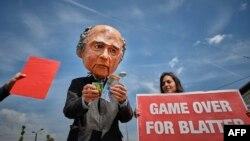 """Một người đàn ông giả trang ông Sepp Blatter, Chủ tịch FIFA, cầm đồng Franc Thuỵ Sĩ, đứng cạnh một phụ với tấm bảng với hàng chữ """"Cuộc chơi dành cho Blatter đã tàn"""" trong cuộc biểu tình phản đối trước sân vận động trường Hallenstadium ở Zurich, Thuỵ Sĩ, 29/5/15"""