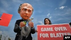 Demonstrators, including one wearing a mask depicting FIFA President Sepp Blatter, protest in front of the Hallenstadium where the 65th FIFA Congress takes place in Zurich, May 29, 2015.
