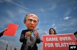 """A man wearing a mask depicting FIFA President Sepp Blatter holding Swiss Francs stands next to a woman holding a banner reading """"Game over for Blatter"""" during a protest held in front of the Hallenstadium where the 65th FIFA Congress takes place in Zurich,"""
