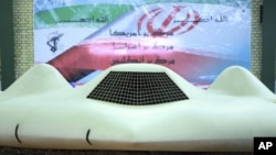 This photo released on Thursday, Dec. 8, 2011, by the Iranian Revolutionary Guards and taken at an undisclosed location claims to show the US RQ-170 Sentinel drone which Tehran says its forces downed earlier this week. In the banner in background depictin