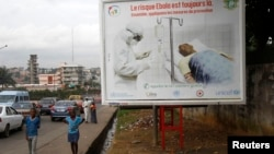 """People walk past a billboard displaying a government message about Ebola that reads: """"The risk of Ebola is still there. Let us apply the protective measures together"""", Abidjan, Ivory Coast, Sept.10, 2014."""