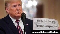 特朗普在白宫东室展示《特朗普被判无罪》的《华盛顿邮报》大字标题。(2020年2月6日)