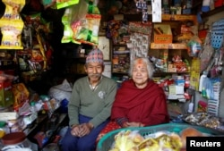 Nhuchhe Bahadur Amatya, 76, a retired accountant at Nepal Electricity Authority, along with his wife, Raywoti Devi Amatya, 74, a housewife, pose for a picture as they sit inside their shop in Lalitpur, Nepal, Feb. 4, 2018.