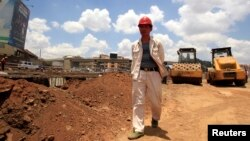 FILE - A site manager from China Wuyi, Sinohydro and Shengeli Engineering Construction Group checks progress on Kenya's Nairobi-Thika highway project, a $28 billion enterprise paid for by China, Kenya and the African Development Bank.