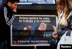 FILE - A poster depicts U.S. District Court Judge Thomas Griesa, overseeing a case in which U.S. hedge funds are suing Argentina, as a vulture in Buenos Aires, Aug. 12, 2014.