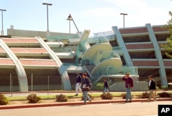 FILE - California State University, Northridge students walk past a parking structure at the Los Angeles campus that collapsed 25 years ago in the Jan. 17, 1994, earthquake.