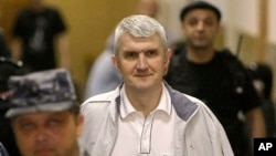 FILE - In this June 3, 2011 file photo, former Yukos CEO Mikhail Khodorkovsky's co-defendant Platon Lebedev, surrounded by guards, walks to a courtroom in Moscow.