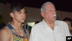Pemain sepakbola Meksiko Alan Pulido (kiri) dalam keterangan pers bersama Gubernur negara bagian Tamaulipas, Egidio Torre Cantu setelah dibebaskan hari Senin pagi (30/5).
