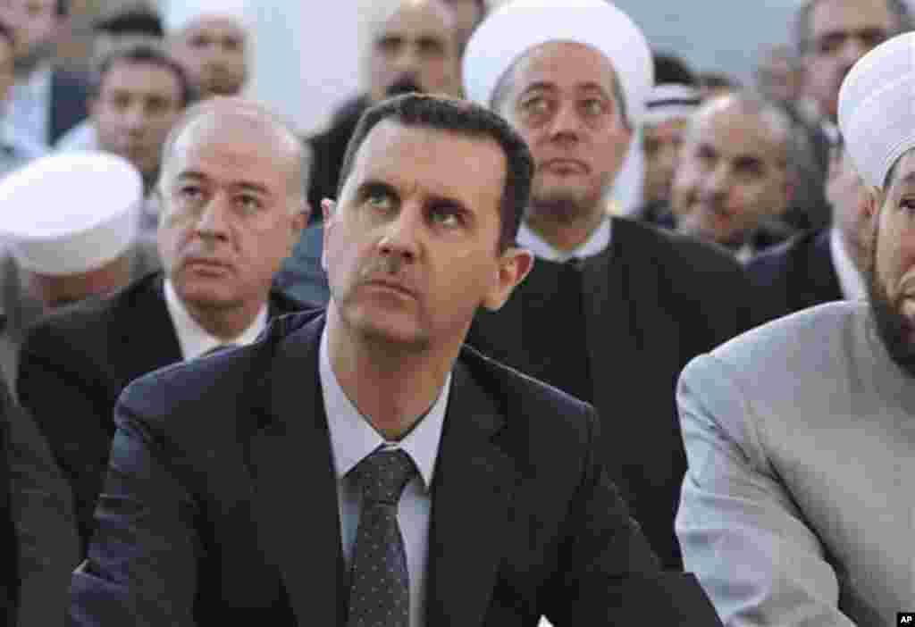 Presiden Suriah Bashar al-Assad menghadiri sholat Idul Fitri di masjid Al-Hamad di Damaskus, Suriah, Minggu (19/8).