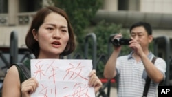 "FILE - In this Aug. 1, 2016 photo, a man films Li Wenzu, wife of imprisoned lawyer Wang Quanzhang. She holds a paper that reads ""Release Liu Ermin"" as she and others stage a protest in Tianjin, China."