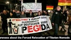 """Manifestantes con un poster que lee """"Sin violencia y unidos contra las guerras religiosas en tierra alemana -PEGIDA"""", durante una protesta en Dresden, Alemania."""