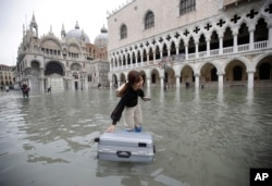 A tourist pushes her floating suitcase in a flooded St. Mark's Square, in Venice, Wednesday, Nov. 13, 2019. The high-water mark hit 187 centimeters late Tuesday, Nov. 12, 2019.