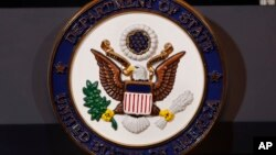 The seal of the State Department is seen on the podium as Secretary of State Mike Pompeo makes a statement about refugees to the media, Sept. 17, 2018, at the State Department in Washington.