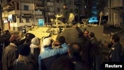 2013年1月28日在塞得港实施宵禁期间,在该市参加游行抗议人群聚集在一辆军用坦克旁边