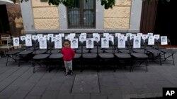 Seorang anak berdiri di depan kursi-kursi kosong dengan potret 43 mahasiswa yang hilang, yang dibuat berderet untuk memperingati sembilan bulan menghilangnya mereka dari Mexico City (27/6). (AP/Marco Ugarte)