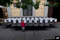 FILE - A child stands before a memorial made up of empty chairs bearing images of 43 missing students, set up to mark the nine-month anniversary of their disappearance, in Mexico City, June 27, 2015.