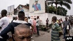 Des badauds regardent des manifestants lors d'une marche contre Kabila, à Kinshasa, le 21 janvier 2018.
